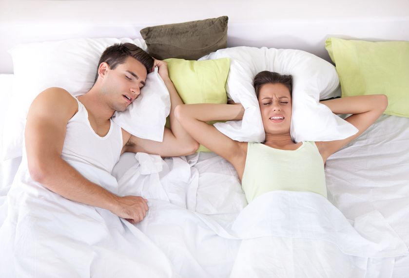 Man snoring, woman covering ears with pillow