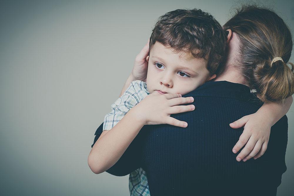Mother holding sad boy against her shoulder
