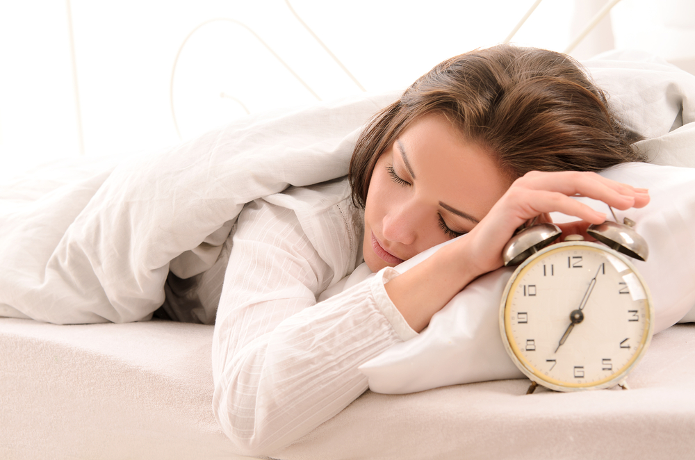 woman with brown hair sleeping in a white bed with her hand on her alarm clock