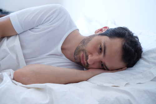 man wearing a white shirt laying in bed awake and worried