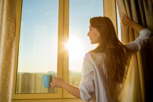 woman waking up early looking at the sun