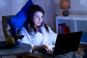 Attractive girl is spending time in front of her laptop at night