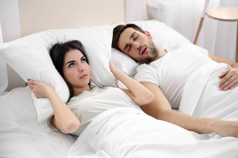 Man snoring while an annoyed woman tries to sleep
