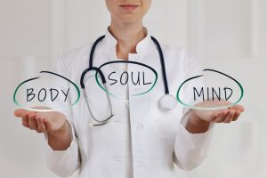 Doctor with palms facing up while the words mind, body, and soul are displayed above hands - Holistic solutions for sleep apnea